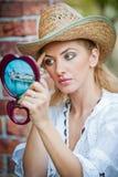 Mujer hermosa con el sombrero y el espejo de paja Imagen de archivo libre de regalías