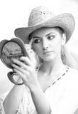Mujer hermosa con el sombrero y el espejo de paja Fotos de archivo libres de regalías