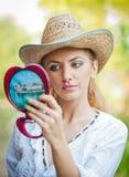 Mujer hermosa con el sombrero y el espejo de paja Fotografía de archivo