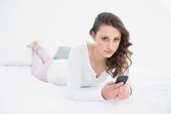 Mujer hermosa con el teléfono móvil en cama Imagen de archivo libre de regalías