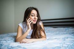 Mujer hermosa con el teléfono móvil en casa en la cama Foto de archivo libre de regalías