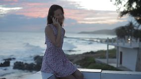 Mujer hermosa con el teléfono móvil en una playa rocosa en la puesta del sol almacen de video