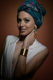 Mujer hermosa con el turbante Hembra atractiva joven con el turbante y los accesorios de oro Mujer de moda de la belleza Imágenes de archivo libres de regalías