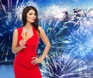 Mujer hermosa con el vidrio del champán sobre el fuego artificial Fotografía de archivo