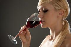 Mujer hermosa con el vino rojo de cristal Foto de archivo libre de regalías