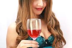 Mujer hermosa con el vino rojo de cristal Imágenes de archivo libres de regalías