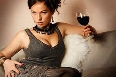 Mujer hermosa con el vino rojo de cristal imagen de archivo