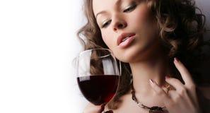 Mujer hermosa con el vino rojo de cristal Foto de archivo