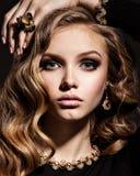 Mujer hermosa con joyería larga del pelo rizado y del oro Imagen de archivo