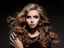 Mujer hermosa con joyería larga del pelo rizado y del oro Imagen de archivo libre de regalías
