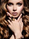 Mujer hermosa con joyería larga del pelo rizado y del oro Foto de archivo libre de regalías