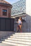Mujer hermosa con la bici vieja delante del edificio de la ciudad Fotos de archivo libres de regalías