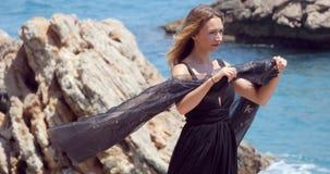 Mujer hermosa con la bufanda negra en vestido negro elegante almacen de metraje de vídeo