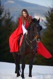 Mujer hermosa con la capa roja con el caballo al aire libre foto de archivo