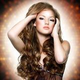 Mujer hermosa con la cara atractiva y los pelos rizados largos Imagen de archivo