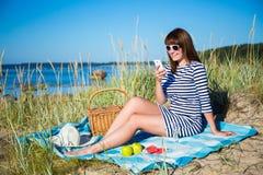 Mujer hermosa con la cesta de la comida campestre y frutas usando el teléfono elegante Imagenes de archivo