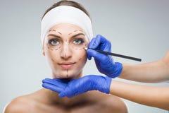 Mujer hermosa con la cirugía plástica, pintura, manos del cirujano plástico Imagenes de archivo