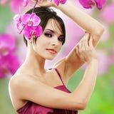 Mujer hermosa con la flor de la orquídea Fotos de archivo
