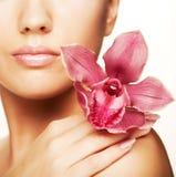 Mujer hermosa con la flor rosada Imagenes de archivo