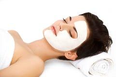 Mujer hermosa con la máscara cosmética en cara. La muchacha consigue el tratamiento Foto de archivo