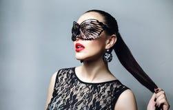 Mujer hermosa con la máscara negra del cordón sobre ella ojos Primer atractivo rojo de los labios y de los clavos Imagen de archivo