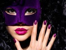 Mujer hermosa con la máscara violeta del teatro en cara y el na púrpura Foto de archivo libre de regalías