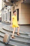 Mujer hermosa con la maleta en la entrada al hotel Imagen de archivo