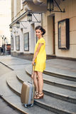 Mujer hermosa con la maleta en la entrada al hotel Fotos de archivo