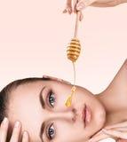 Mujer hermosa con la miel en cara imagen de archivo