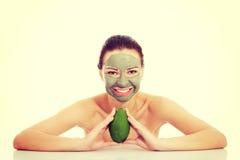 Mujer hermosa con la máscara facial que sostiene el aguacate Foto de archivo libre de regalías