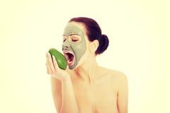Mujer hermosa con la máscara facial que sostiene el aguacate Fotos de archivo
