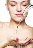 Mujer hermosa con la piel limpia con el chapoteo del agua Foto de archivo libre de regalías