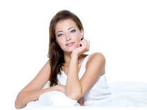 Mujer hermosa con la piel limpia que se sienta en el sofá