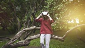 Mujer hermosa con la realidad virtual que se sienta en tronco de árbol en parque al aire libre Dispositivo de los vidrios de las  foto de archivo