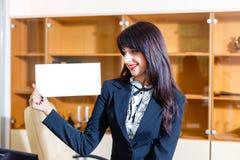 Mujer hermosa con la tarjeta vacía en oficina Imagen de archivo libre de regalías