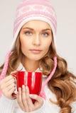 Mujer hermosa con la taza roja Foto de archivo libre de regalías