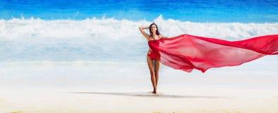 Mujer hermosa con la tela del vuelo del color rojo foto de archivo