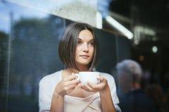 Mujer hermosa con la ventana del restaurante de la taza de café Foto de archivo libre de regalías