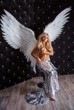 Mujer hermosa con las alas blancas en fondo negro foto de archivo libre de regalías