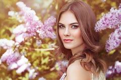 Mujer hermosa con las flores de la lila Imagen de archivo