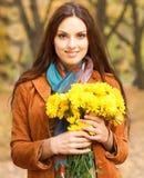 Mujer hermosa con las flores en parque del otoño Foto de archivo libre de regalías