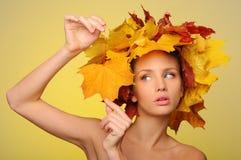 Mujer hermosa con las hojas de otoño en amarillo Imagen de archivo libre de regalías