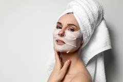 Mujer hermosa con las m?scaras de la cara y de ojo del algod?n contra fondo ligero fotos de archivo
