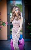 Mujer hermosa con las maletas que salen del hotel en una ciudad grande Pelirrojo atractivo con las gafas de sol y el vestido eleg Fotos de archivo libres de regalías