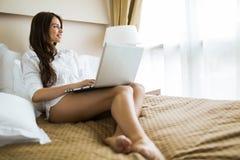 Mujer hermosa con las piernas largas atractivas en camisa usando un cuaderno adentro Imagenes de archivo