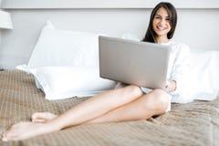 Mujer hermosa con las piernas largas atractivas en camisa usando un cuaderno adentro Imágenes de archivo libres de regalías