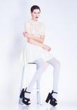 Mujer hermosa con las piernas largas en la presentación blanca del vestido y de los tacones altos Imágenes de archivo libres de regalías