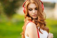 Mujer hermosa con los auriculares que escucha la música Foto de archivo libre de regalías