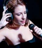 Mujer hermosa con los auriculares y el canto del mic Imagenes de archivo