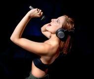 Mujer hermosa con los auriculares y el canto del mic Fotos de archivo